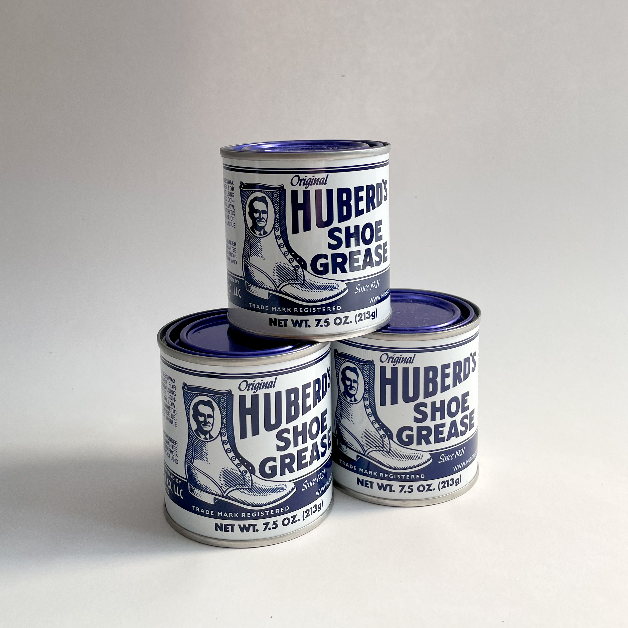 Three Huberd's Shoe Grease cans in a pyramid