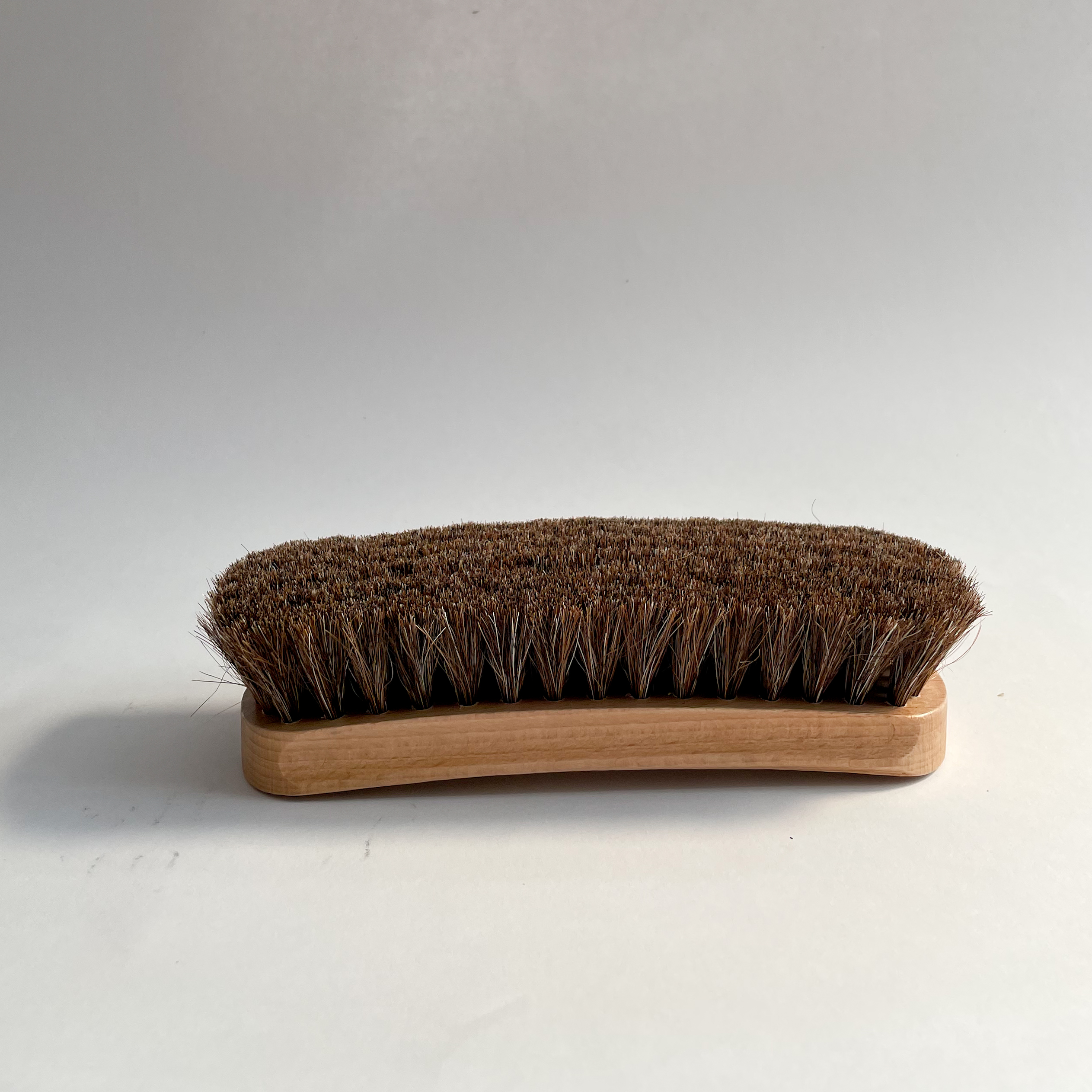 A single large buffing brush with it's bristles facing upwards