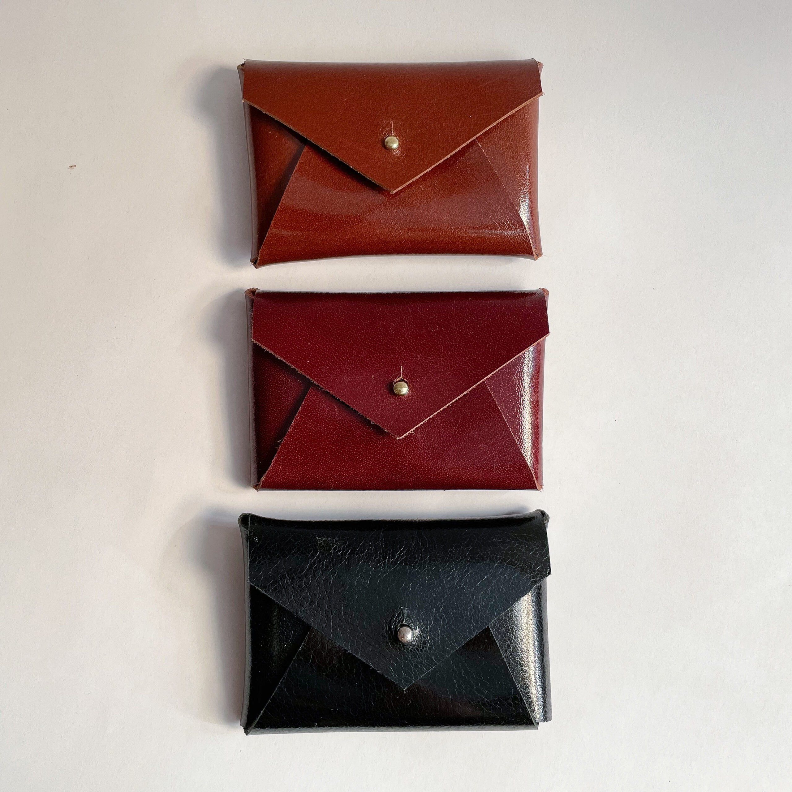 Three leather card cases laying on their back