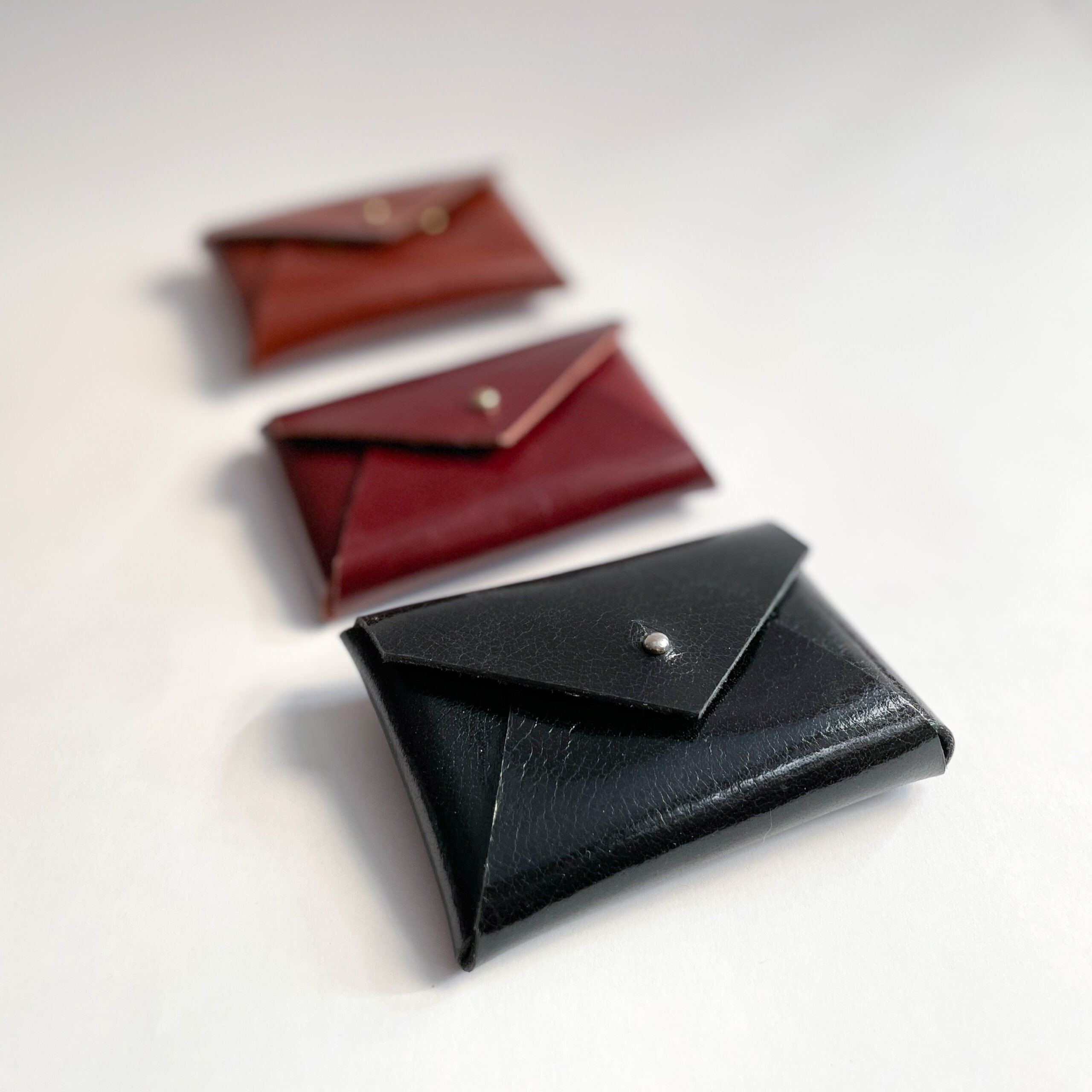 Three leather card cases, with the black on in front, in focus