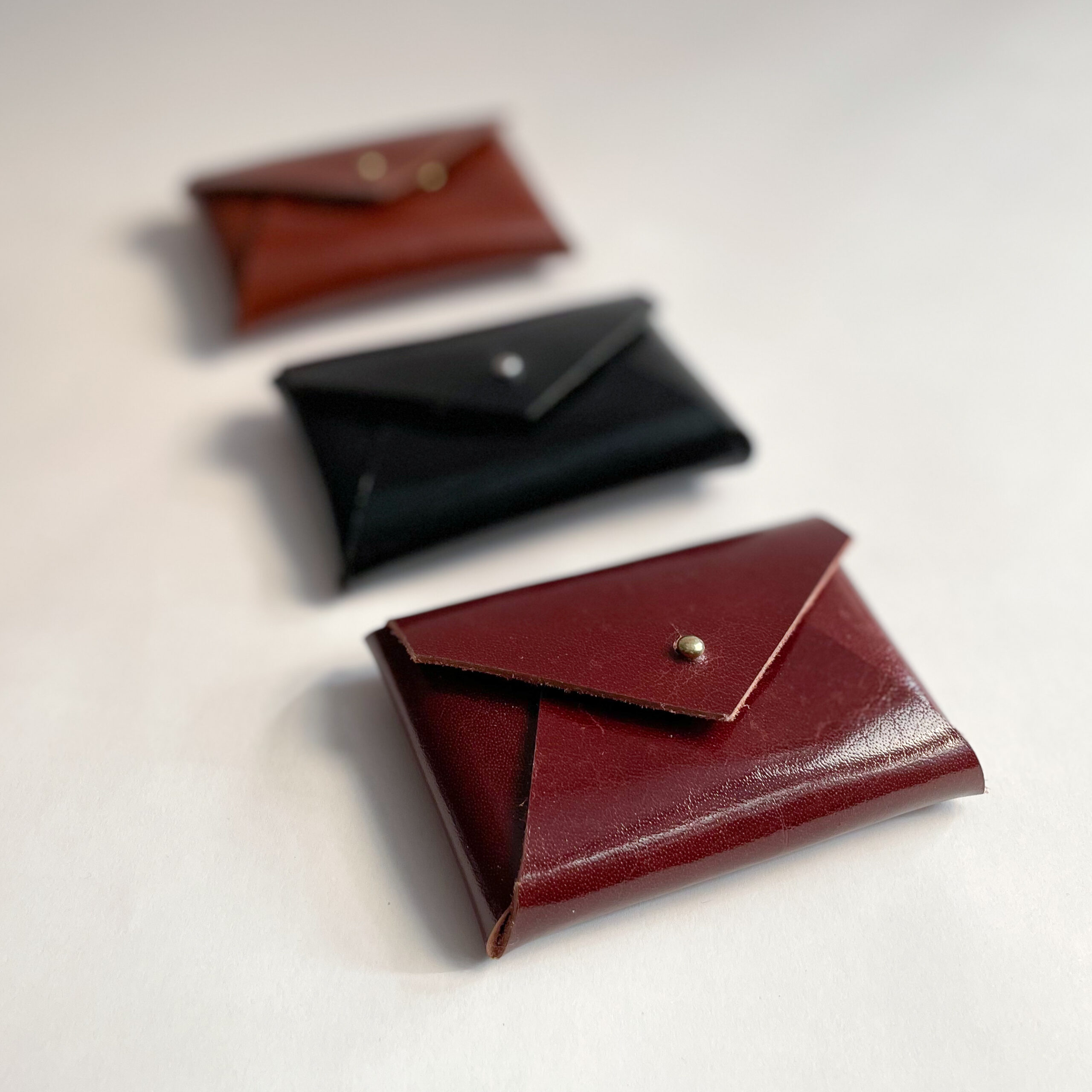 Three Leather Card Cases with the Maroon one in front