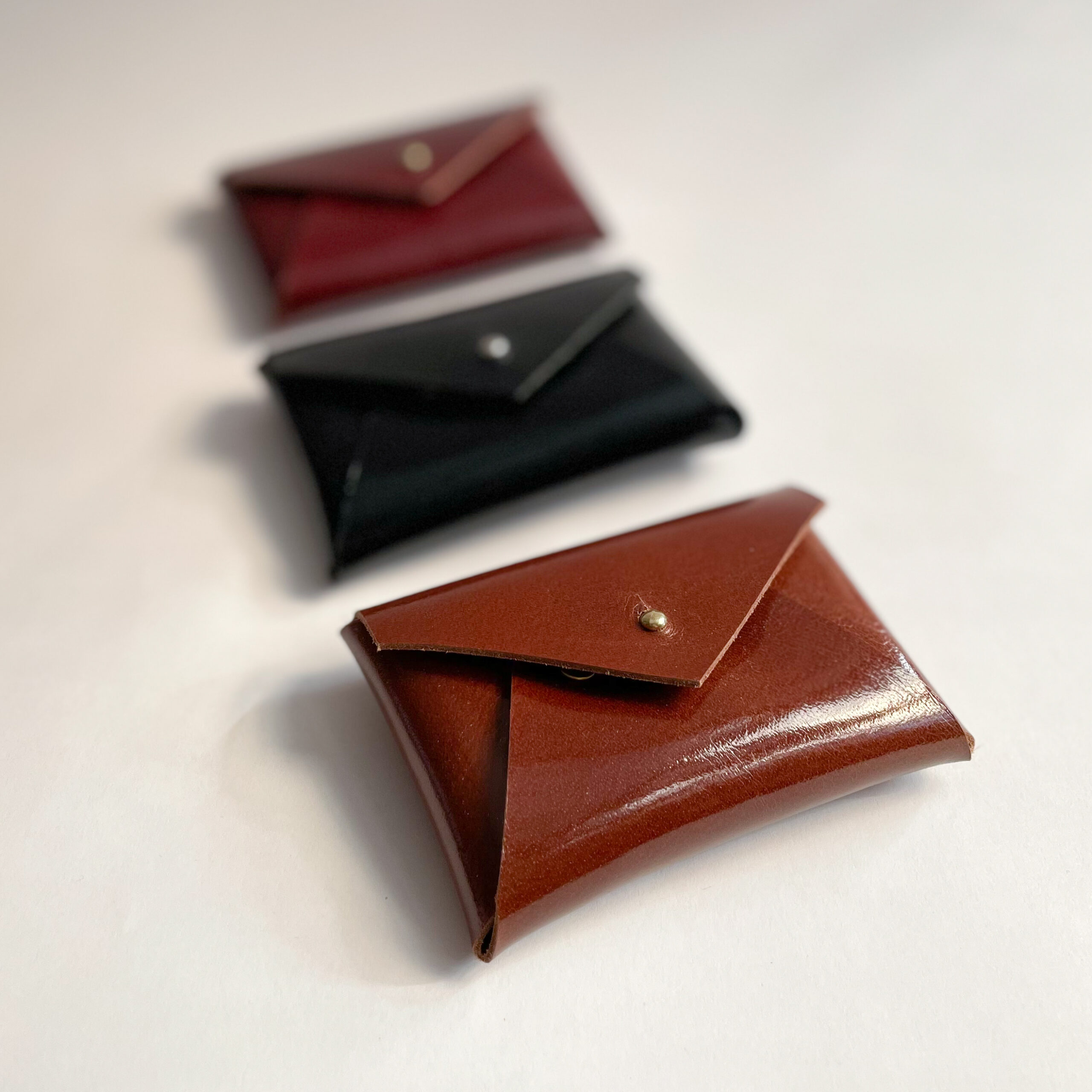 Three leather card cases with the Medium Brown one in the front