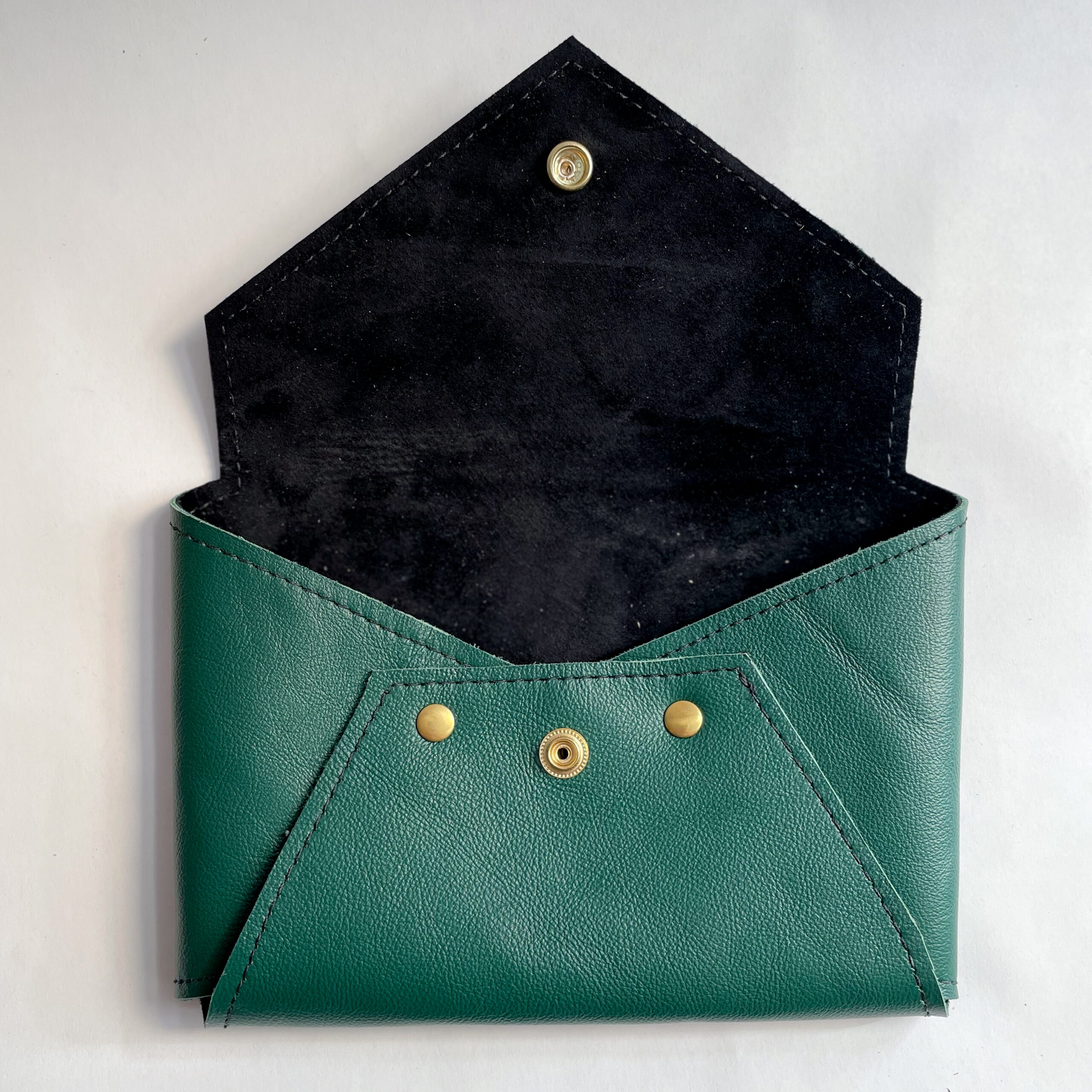 Green Envelope Clutch sitting open to reveal black lining