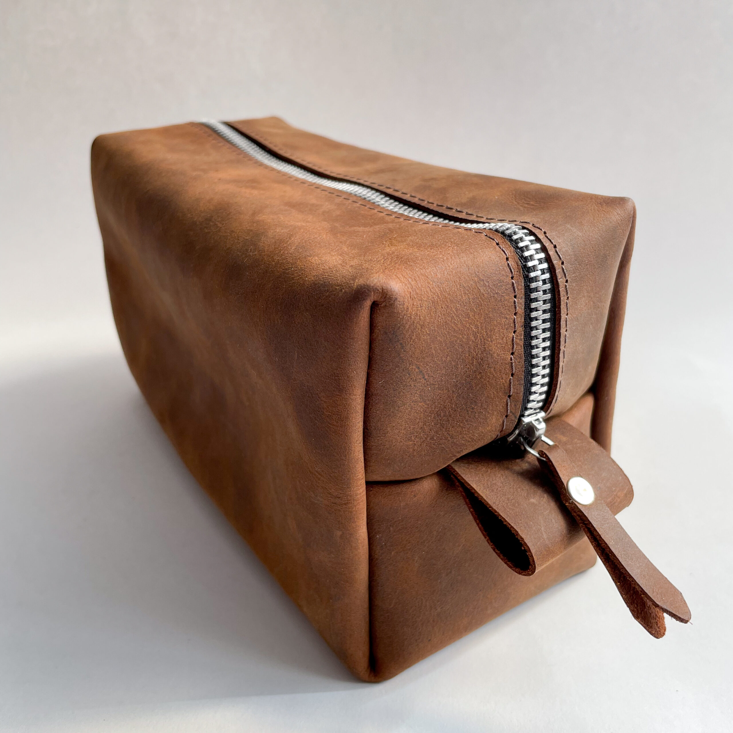 A brown leather dopp kit
