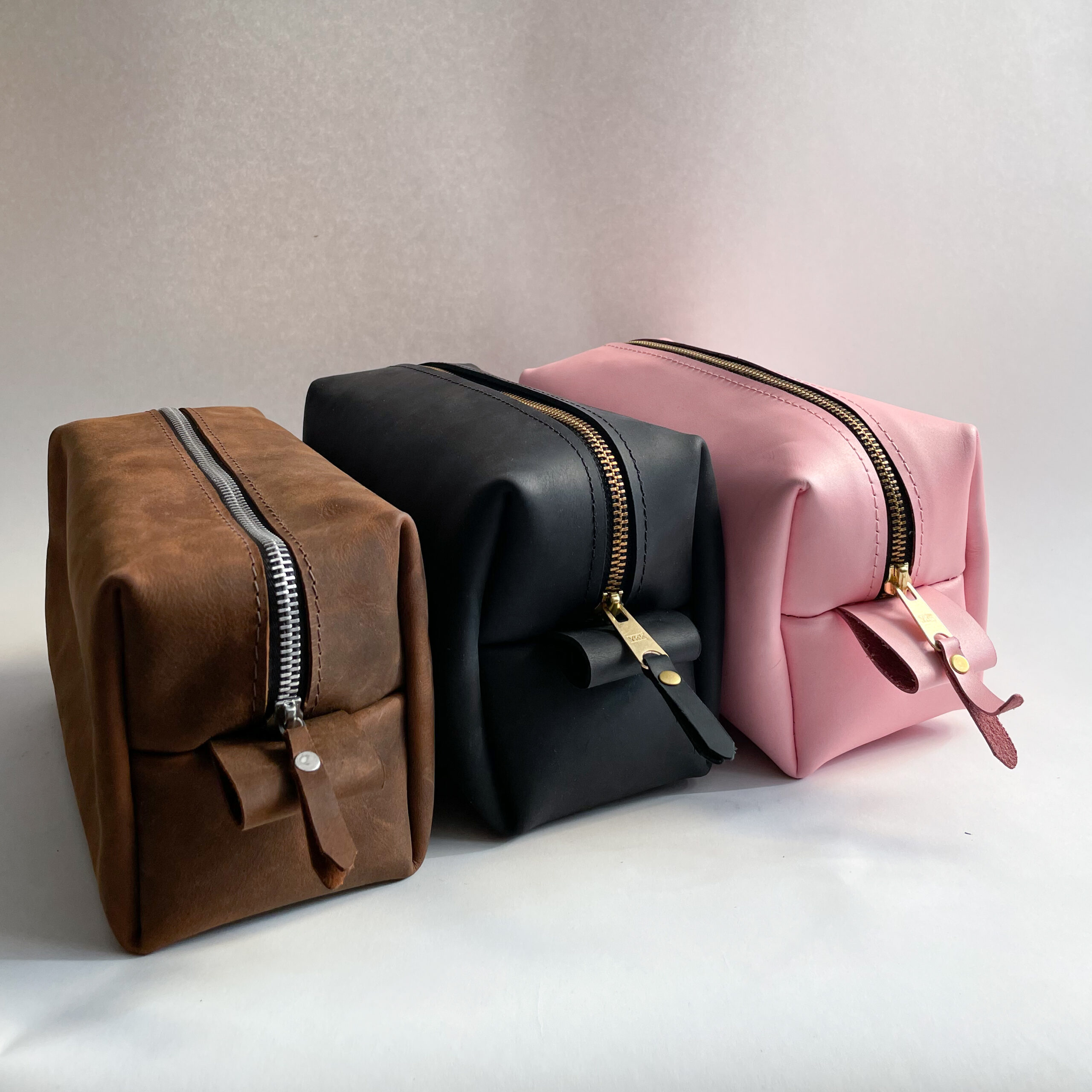 Three leather dopp kits, sitting side by side, (brown, black, pink, from left to right)
