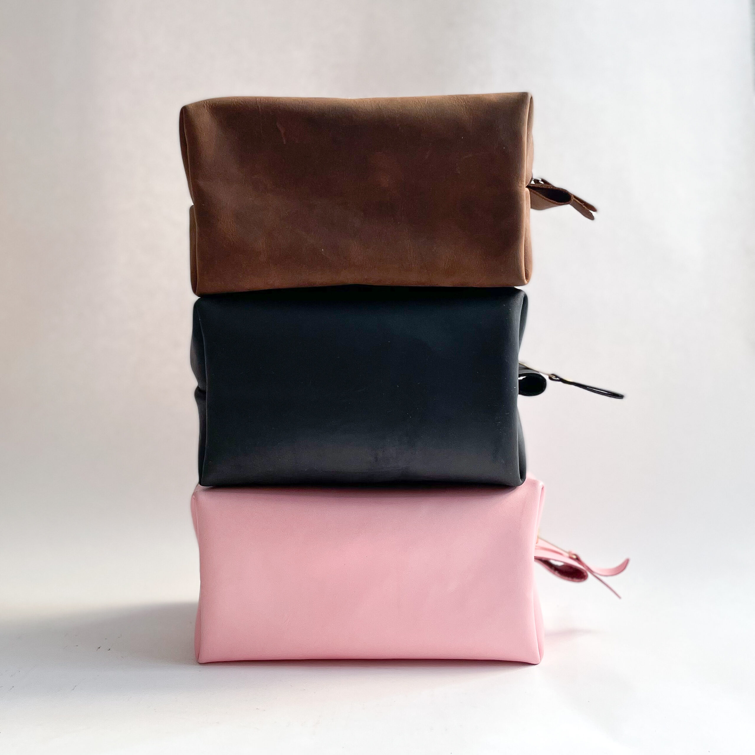 A brown dopp kit, a black dopp kit and a pink dopp kit, sitting in a stack, from the side